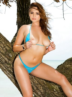 Sasha, one of the beautiful Penthouse Club Keygirls, unties her swimsuit and relaxes naked against the trunk of a leaning tropical tree near a nude be