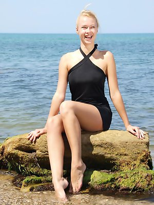 Beautiful Angie T slips out of a black halter and spreads herself on the rocks.